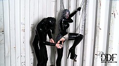 Dude in a gimp suit fucks his latex-clad lover with a big dildo