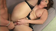 The busty cougar lies on the couch and spreads her hot legs to get pounded deep