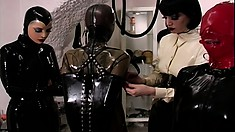 Latex slave and mistresses are in the dungeon tying her up for torture