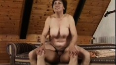 Busty mature lady Valda has a young guy's cock filling her hairy peach