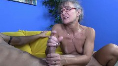 Horny granny strips naked to jerk off a hot tattooed younger man on the couch