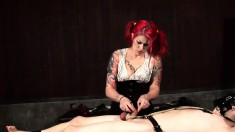 Dominatrix with flaming hair restrains her bound slave's cock and balls with chains
