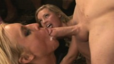 Two gorgeous and lustful blondes working their hot lips on a big dick