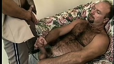 Chubby guy sits on the couch and offers his gay lover a great blowjob