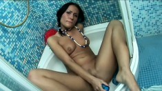 Striking young brunette Nila has fun with a blue sex toy in the shower