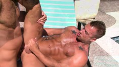 Two handsome gay lovers indulging in steamy anal action by the pool